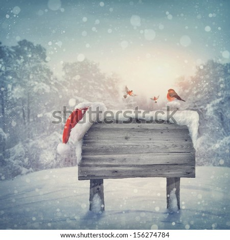 Wooden sign and santa hat in winter forest - stock photo