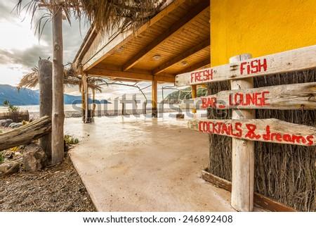 Wooden sign at beach bar on Bussaglia beach near Porto on west coast of Corsica - stock photo