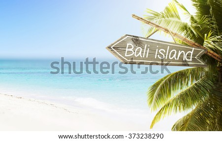 Wooden sign Bali Island on tropical white sand beach summer background. Lush tropical foliage and sunshine. Blue ocean at perfect day. No people. - stock photo