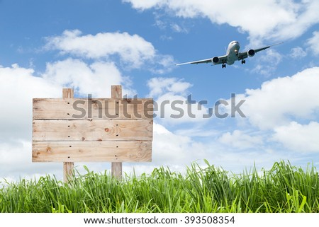 wooden sign board  and Passenger airplane landing with green grass , blue sky background. - stock photo