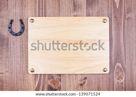Wooden sign board with horseshoe on wood wall background - stock photo
