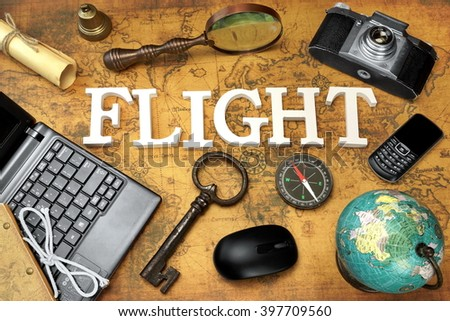 Wooden Sign Flight, Laptop, Vintage 35mm Photo Camera, Retro Key,  Globe, Magnifier, Compass, GSM Phone, Computer Mouse And Letter On The Old Map, Flat Lay, Top View - stock photo