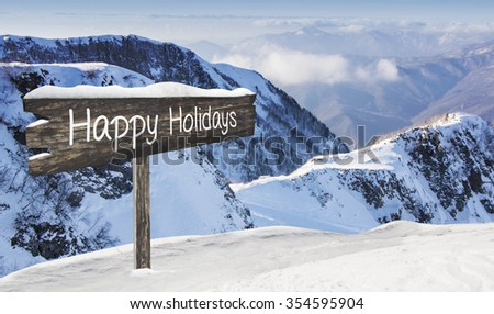 Wooden sign Happy Holidays. Ski-track with Caucasus mountains on background. Ski vacation panorama on top of the mountain. No people.