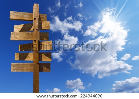 Wooden Sign on Blue Sky with Clouds / Wooden old brown crossroad sign on a blue sky with clouds - stock photo