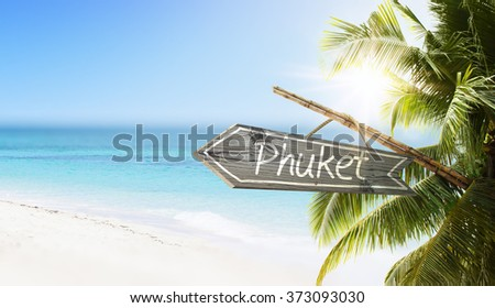 Wooden sign Phuket on tropical white sand beach summer background. Lush tropical foliage and sunshine. Blue ocean at perfect day. No people. - stock photo