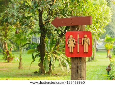 Wooden Sign pointing direction go to toilet - stock photo