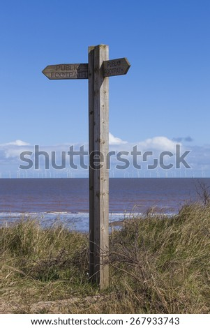 Wooden sign post at Spurn Point nature reserve with offshore wind farm in background, Yorkshire, Great Britain
