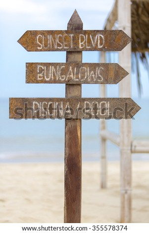 Wooden sign post standing on the beach and providing the direction to the Bungalows and the swimming pool on the beach in Punta Sal, Peru - stock photo