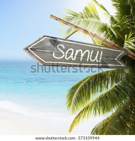 Wooden sign Samui on tropical white sand beach summer background. Lush tropical foliage and sunshine. Blue ocean at perfect day. No people. - stock photo
