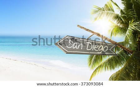 Wooden sign San Diego on tropical white sand beach summer background. Lush tropical foliage and sunshine. Blue ocean at perfect day. No people. - stock photo