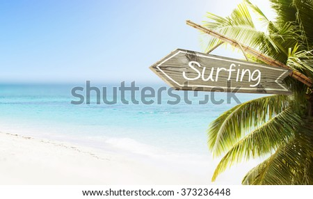 Wooden sign Surfing on tropical white sand beach summer background. Lush tropical foliage and sunshine. Blue ocean at perfect day. No people.  - stock photo