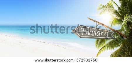 Wooden sign Thailand on tropical white sand beach summer background. Lush tropical foliage and sunshine. Blue ocean at perfect day. No people. - stock photo