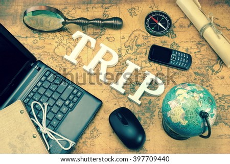 Wooden Sign Trip, Laptop, Computer Mouse, Vintage Globe And Retro Magnifier, Modern Compass, GSM Phone And Letter On The Old Map, Toned Image,  Flat Lay, Overhead View - stock photo