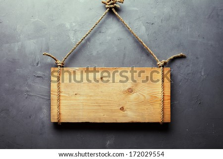 Wooden signboard hanging on rope on gray textured wall - stock photo