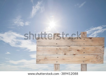 wooden signboard on blue sky and sun light for summer background with copy space - stock photo