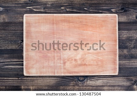 Wooden signboard on dark wood planks background - stock photo