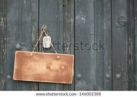 Wooden signboard with army dog tags hanging on wood planks background - stock photo