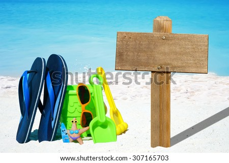 Wooden signboard with copy space and colorful beach toys on the seaside