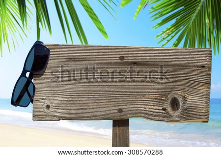 Wooden signboard with copy space and sunglasses under palm fronds on the summer beach