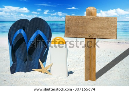 Wooden signboard with copy space, flip flops and suntan lotion on the summer beach