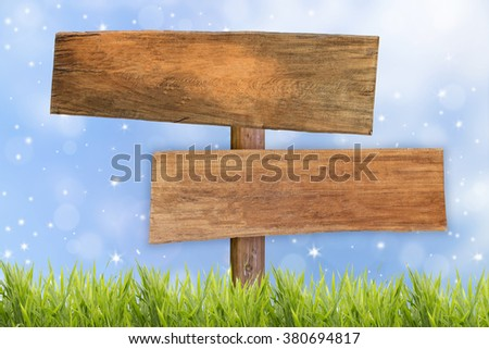 wooden signboard with grass field and blue blurred background