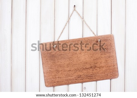Wooden signboard with rope hanging on white wood planks background - stock photo