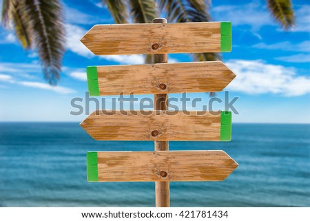 wooden signpost in the meadow with copyspace on the ocean and palms background - stock photo