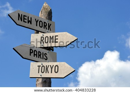Wooden signpost with four arrows, capital cities - New York, Rome, Paris, Tokyo. Great for topics like traveling, international business etc. - stock photo