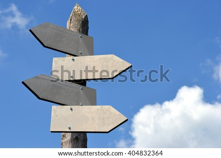 Wooden signpost with four arrows - great to type some information on it (copy space). - stock photo