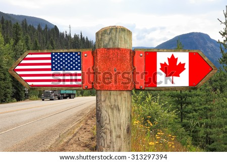 Wooden signpost with two arrows - american and canadian national flags on the highway road with nature landscape in the background. Canada and America moving direction sign - stock photo