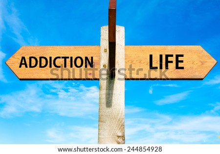 Wooden signpost with two opposite arrows over clear blue sky, Addiction and Life signs, Choice conceptual image  - stock photo