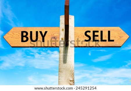 Wooden signpost with two opposite arrows over clear blue sky, Buy versus Sell messages - stock photo