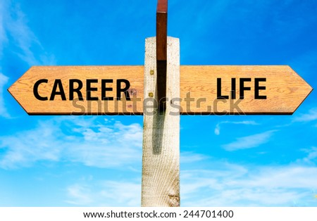 Wooden signpost with two opposite arrows over clear blue sky, Career and Life signs, Work Life Balance conceptual image - stock photo