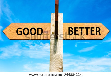 Wooden signpost with two opposite arrows over clear blue sky, Good versus Better messages, Lifestyle change conceptual image - stock photo