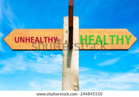 Wooden signpost with two opposite arrows over clear blue sky, Healthy versus Unhealthy messages, Healthy Lifestyle conceptual image - stock photo