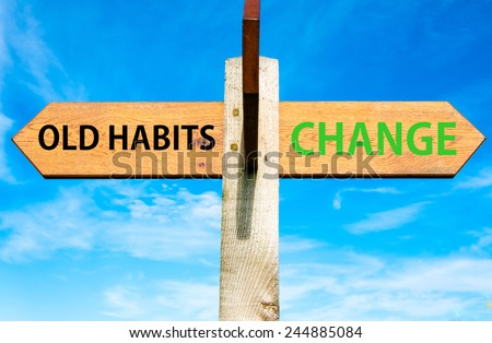 Wooden signpost with two opposite arrows over clear blue sky, Old Habits versus Change messages, Lifestyle change conceptual image - stock photo