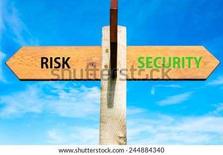 Wooden signpost with two opposite arrows over clear blue sky, Risk versus Security messages, Lifestyle change conceptual image - stock photo