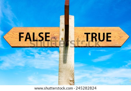 Wooden signpost with two opposite arrows over clear blue sky, True versus False messages - stock photo