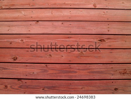 Wooden slats on a weathered wooden deck with redwood stain. - stock photo