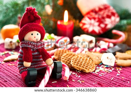 Wooden smiling doll sitting with sweet striped candy canes on christmas background. Closeup indoors multicolored horizontal  image - stock photo