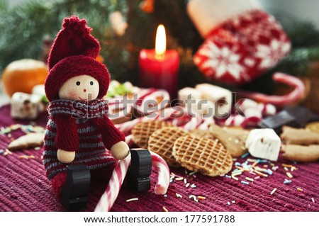 Wooden smiling doll with sweet striped candy canes on christmas background. Closeup. - stock photo