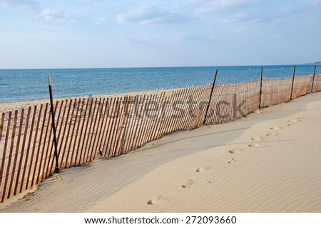 wooden snow fence on Lake Michigan shoreline - stock photo