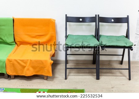 Wooden sofa with blankets and two black chairs are in domestic room - stock photo