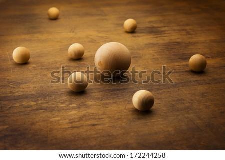 Wooden spheres on a grungy old desk, representing a planetary or atomic particle formation.  - stock photo
