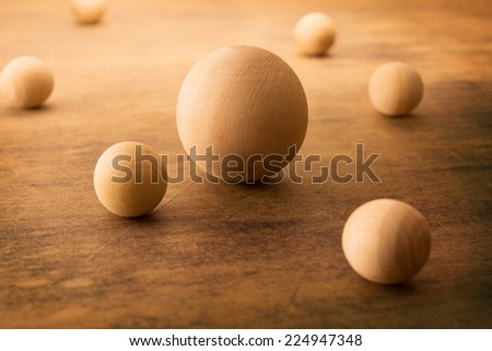 Wooden spheres on a old grungy surface, representing a planetary or atomic particle formation.  - stock photo