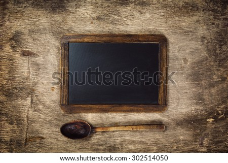 Wooden spoon and Blackboard on a rustic dark background - stock photo