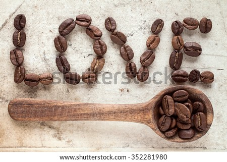 Wooden spoon and coffee beans used to spell love on old canvas - stock photo