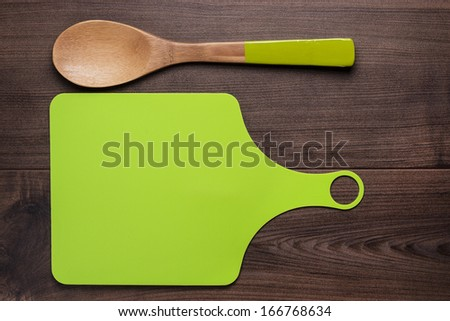 wooden spoon and cutting board on the brown table - stock photo