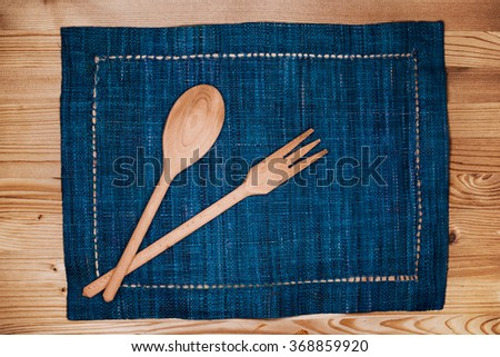 Wooden spoon and fork on blue placemat over a wooden table - stock photo