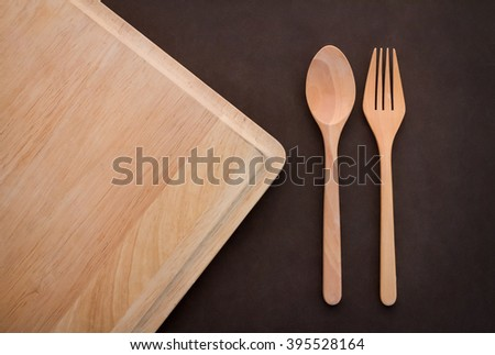 wooden spoon and fork on cutting pad on dark brown background  with copy space for your text - stock photo
